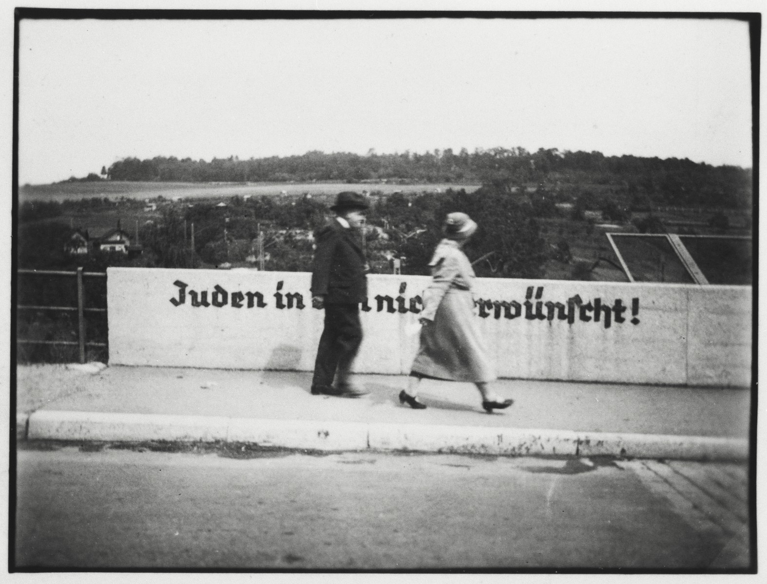 "A Jewish gentleman and his daughter cross the Stuttgarter Strasse bridge in Ulm that is painted with the sign ""Jews are not desireable in Ulm"".  Pictured are Jacob Guggenheimer and Irene Guggenheimer Einstein (the grandfather and mother of the donor)."