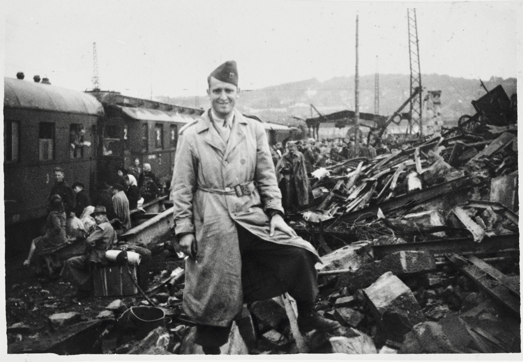 An American soldier poses next to a huge pile of rubble alongside a railroad after the war.