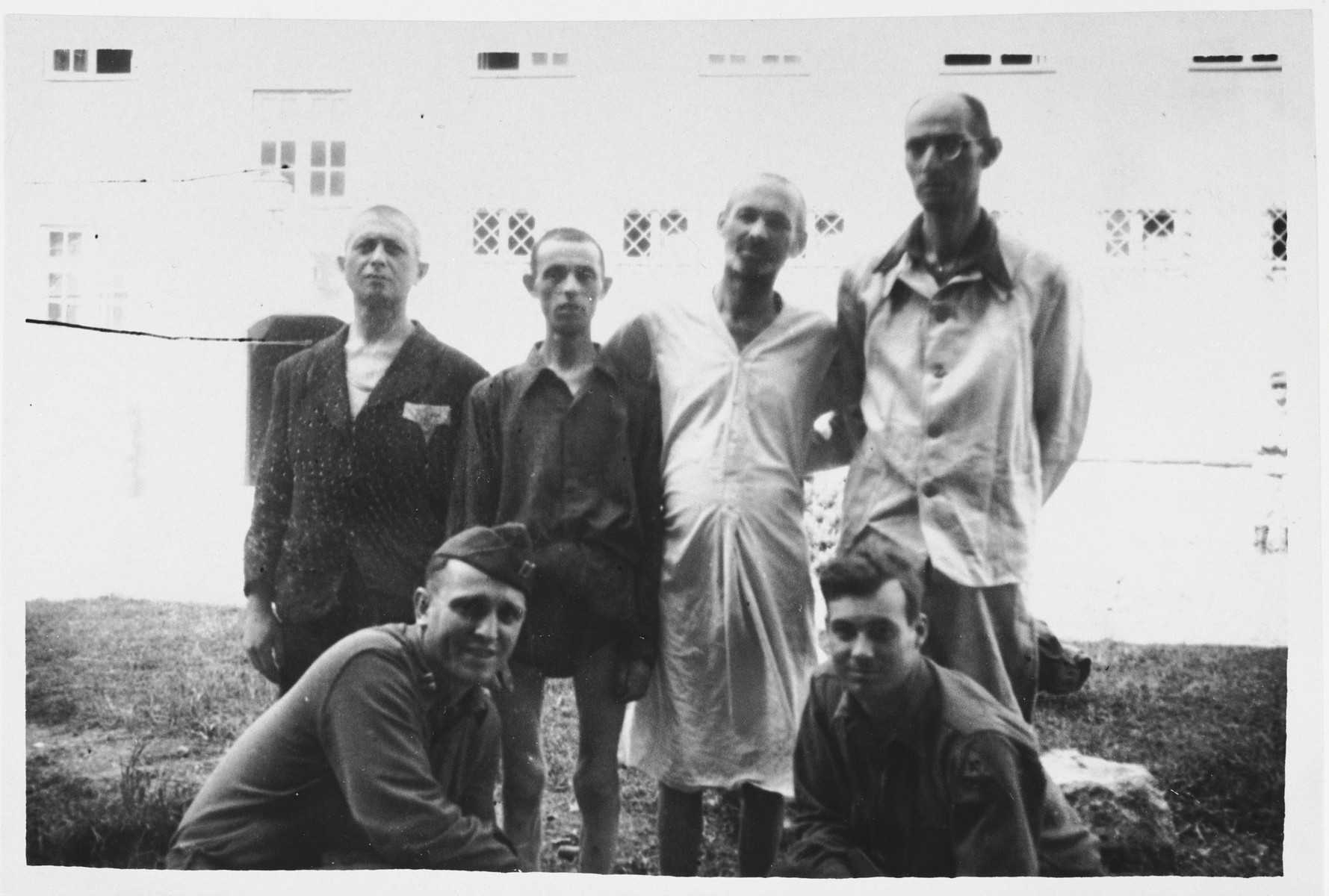 Four survivors of Dachau and Buchenwald pose with Pfc. Robert Kenser and another U.S. soldier at a medical facility in Garmisch-Partenkirchen, where they have come to convalesce.