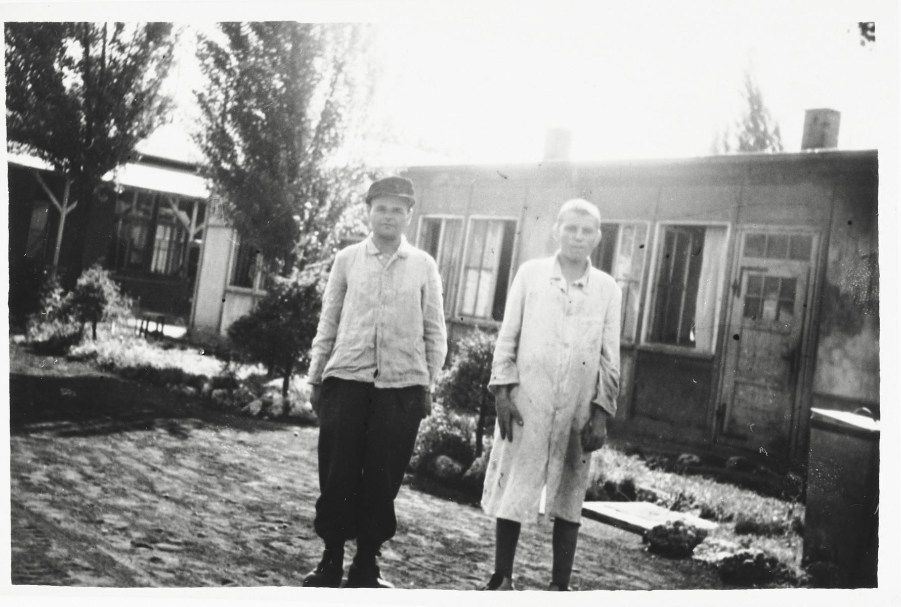Two young survivors of Dachau pose outside [possibly an administrative] building in the camp complex.