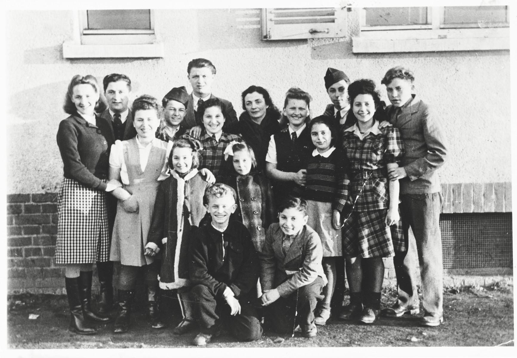 Group portrait of children in the Zeilsheim children's center.  Szlomo Waks is pictured kneeling in the front row, left.