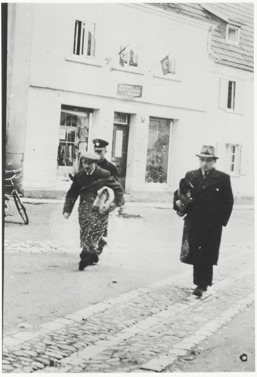 Two Jewish men, carrying blanket rolls, are escorted to a police station following their arrest. Arthur Einstein is pictured on the right. On the left is Max  Heimbach.   Mr. Einstein immigrated to the United States on December 22, 1939, while Mr. Heimbach emigrated to Brazil.