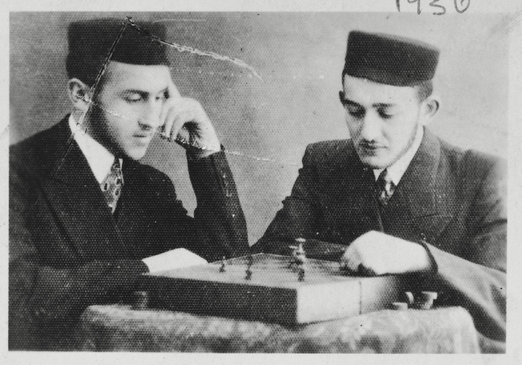 Two Hasidic youths play a game of chess.  Tadek Majranc is pictured on the right.