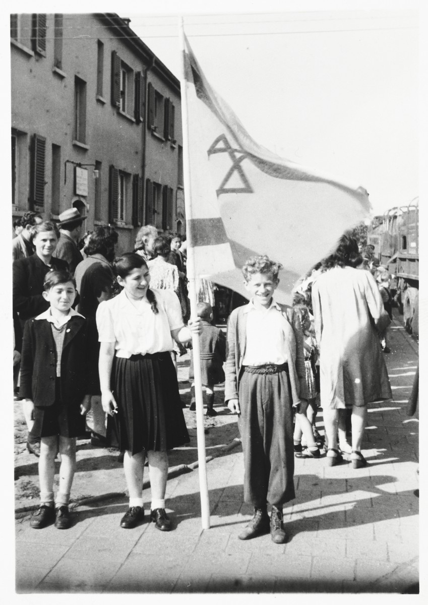 Two children pose with a Zionist flag while preparing for a demonstration in the Zeilsheim DP camp.  Szlomo Waks is standing to the right of the flag.