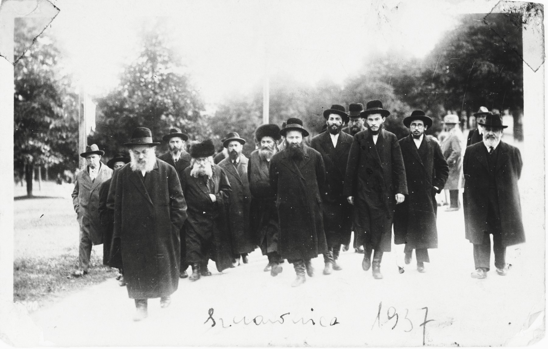 The Gerer Rebbe, Rabbi Abraham Mordecai Alter, walks along a street of a resort town accompanied by a group of his followers.  Also pictured are Rav Bunim Levin (brother of the Rabbi of Bedzin) and Rabbi Meir Alter (the eldest son of the Gerer rebbe).
