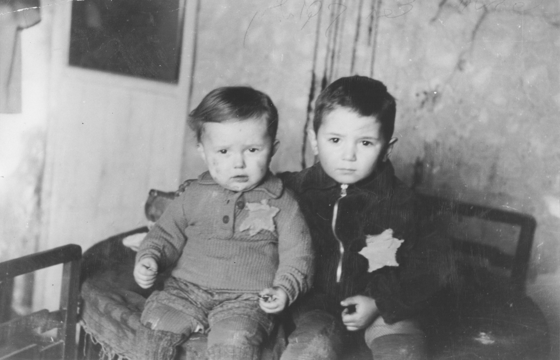 "Portrait of two young boys wearing Jewish badges in the Kovno ghetto taken shortly before their round-up in the March 1944 ""Children's Action"".  Pictured are Avram (5 years) and Emanuel Rosenthal (2 years).  Emanuel was born in the Kovno ghetto.  The children, who were deported in the March 1944 ""Children's Action,"" did not survive.  Their uncle, Shraga Wainer, who had asked George Kadish to take this photograph, received a copy of it from the photographer after the war in the Landsberg displaced persons camp."