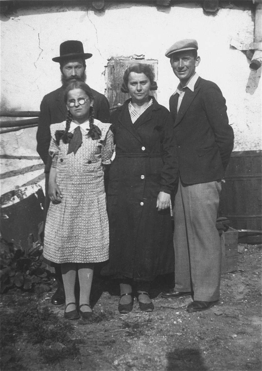 Portrait of the Weinstein family outside their home in Kobluszowa.  Pictured from left to right are: Reuven (behind), Shaindel (in front) and Bluma Gela Weinstein, and David Saleschutz.