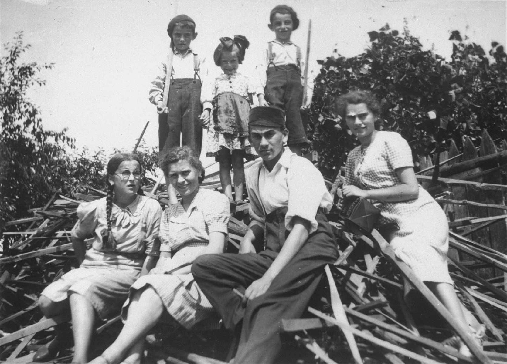Members of the extended Saleschütz family pose on a pile of wood in Kolbuszowa.  Pictured in the back row from left to right are: Shulem, Rozia; Shloime, the children of Leibush Saleschütz.  Seated in front are Shaindel Weinstein, the daughter of Bluma Saleschütz. Matla, Naftali and Rachel Saleschütz.