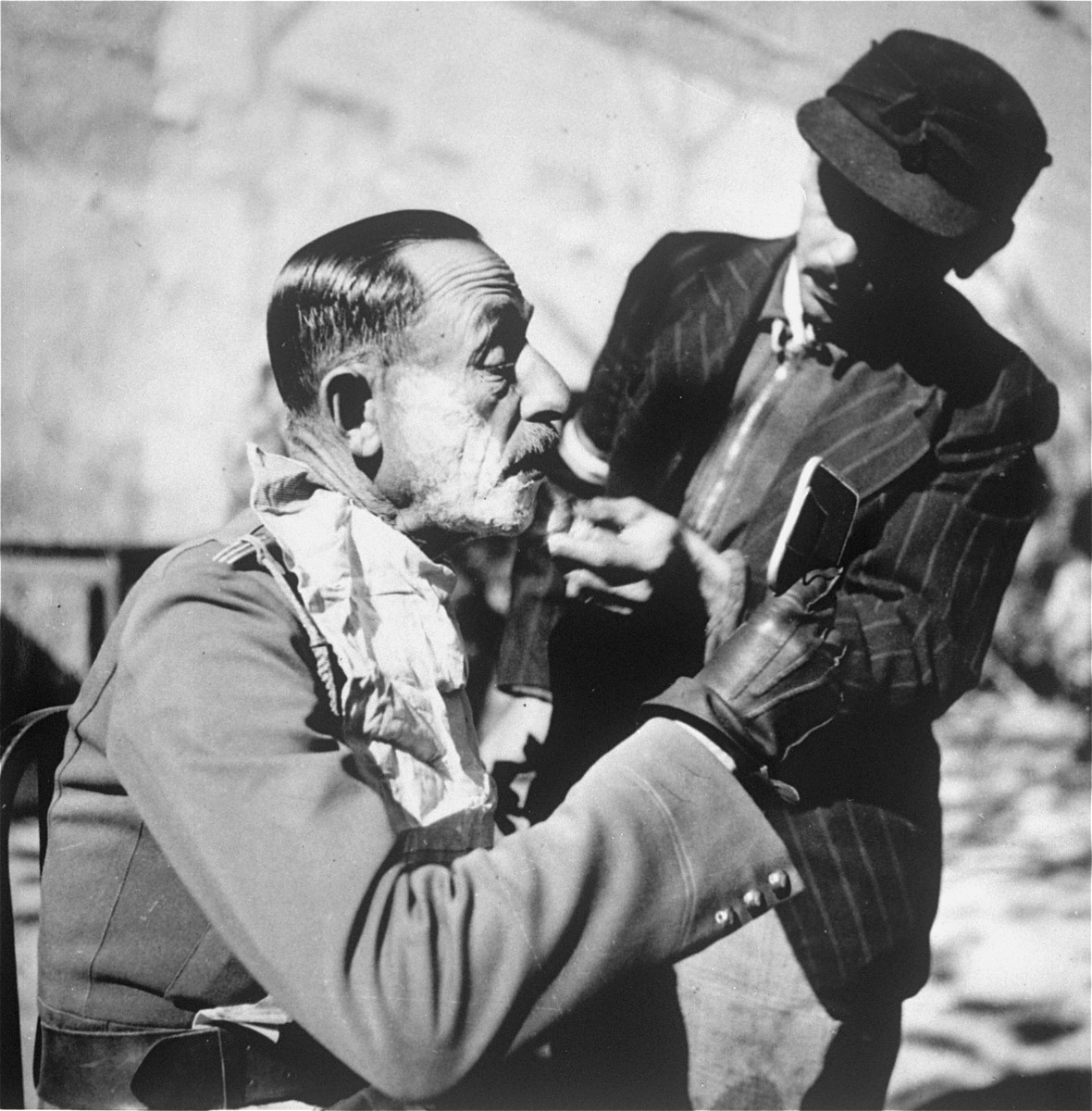 An officer being shaved at an unidentified labor camp in Hungary.