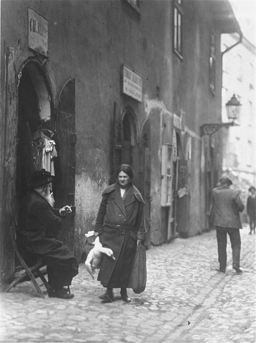 A Jewish woman carries a goose along a street in the Kazimierz quarter of Krakow.