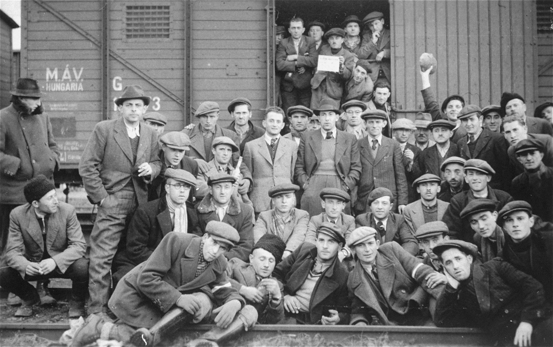 The donor's father, Kalman Yoszef (holding a bottle), among a group of  Hungarian Jews posing in front of a train before their transfer to a Hungarian labor camp.  One of the conscripts in the train holds a sign in Yiddish with a number underneath (illegible).