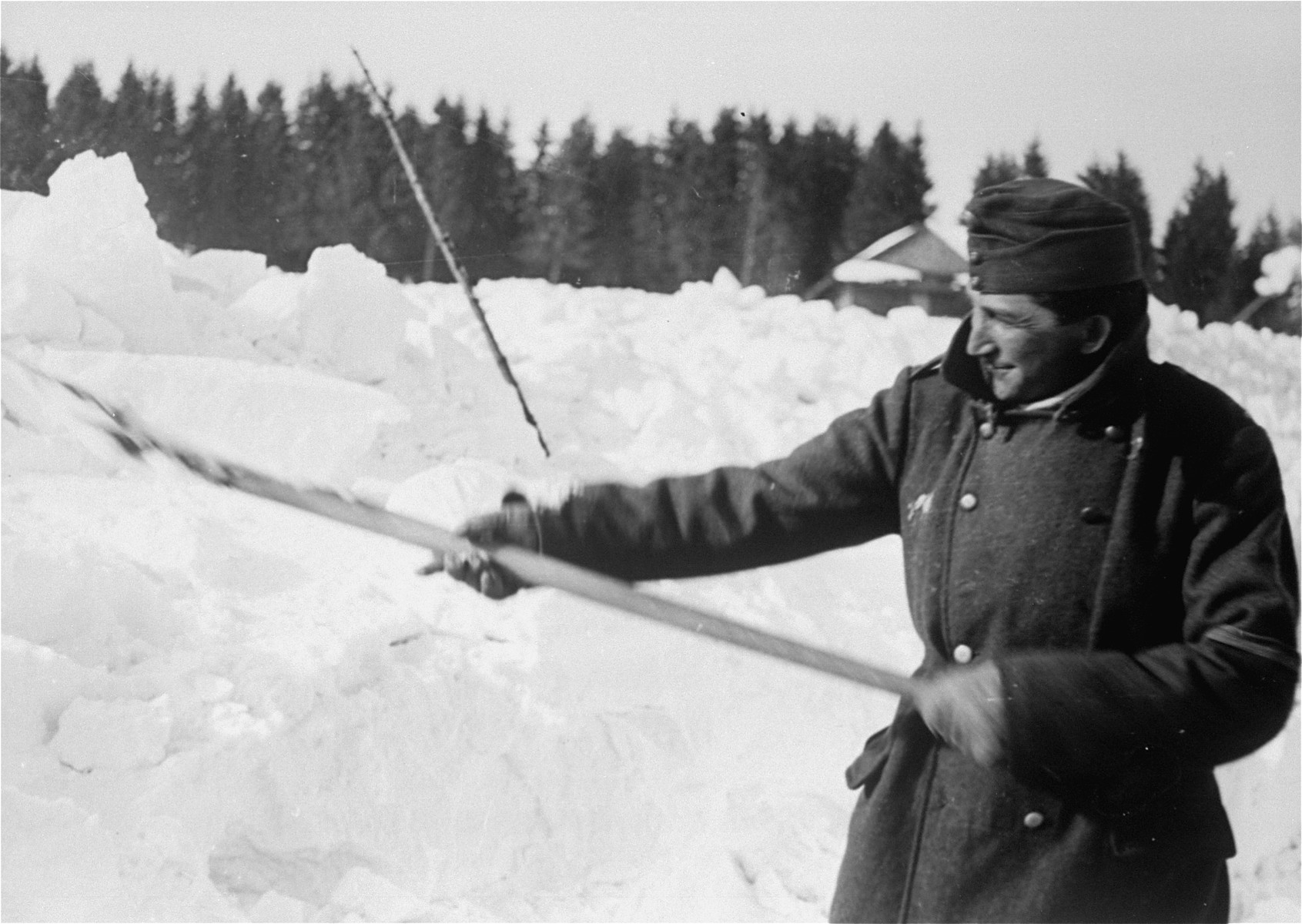 A Jewish conscript in Company 108/57 of the Hungarian Labor Service clearing snow from a road.