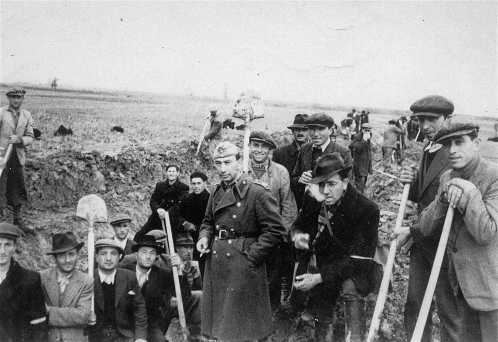 Jewish members of an Hungarian labor battalion pose with shovels at a work site.  Among those pictured is Salomon Belo from the town of Bene (third from the left).