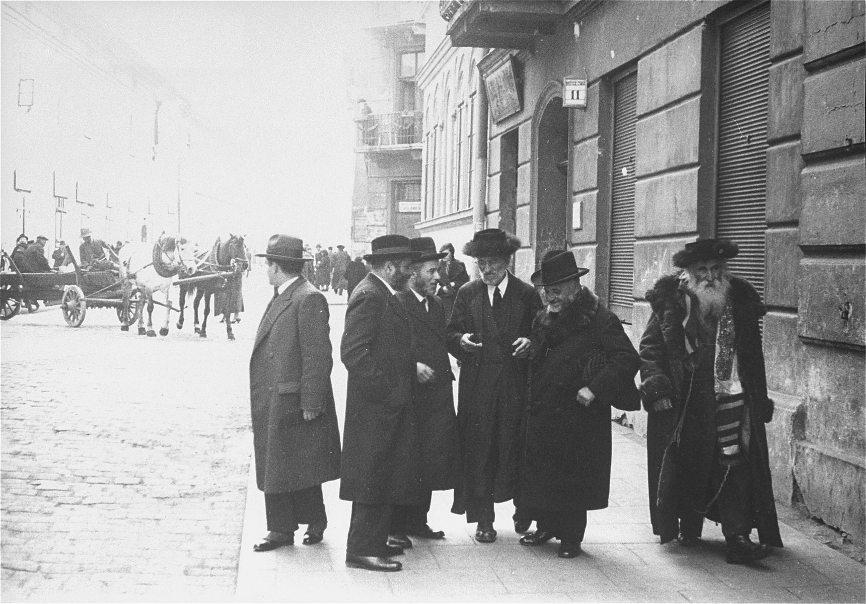 Religious Jews converse on a street corner in the Kazimierz quarter of Krakow.