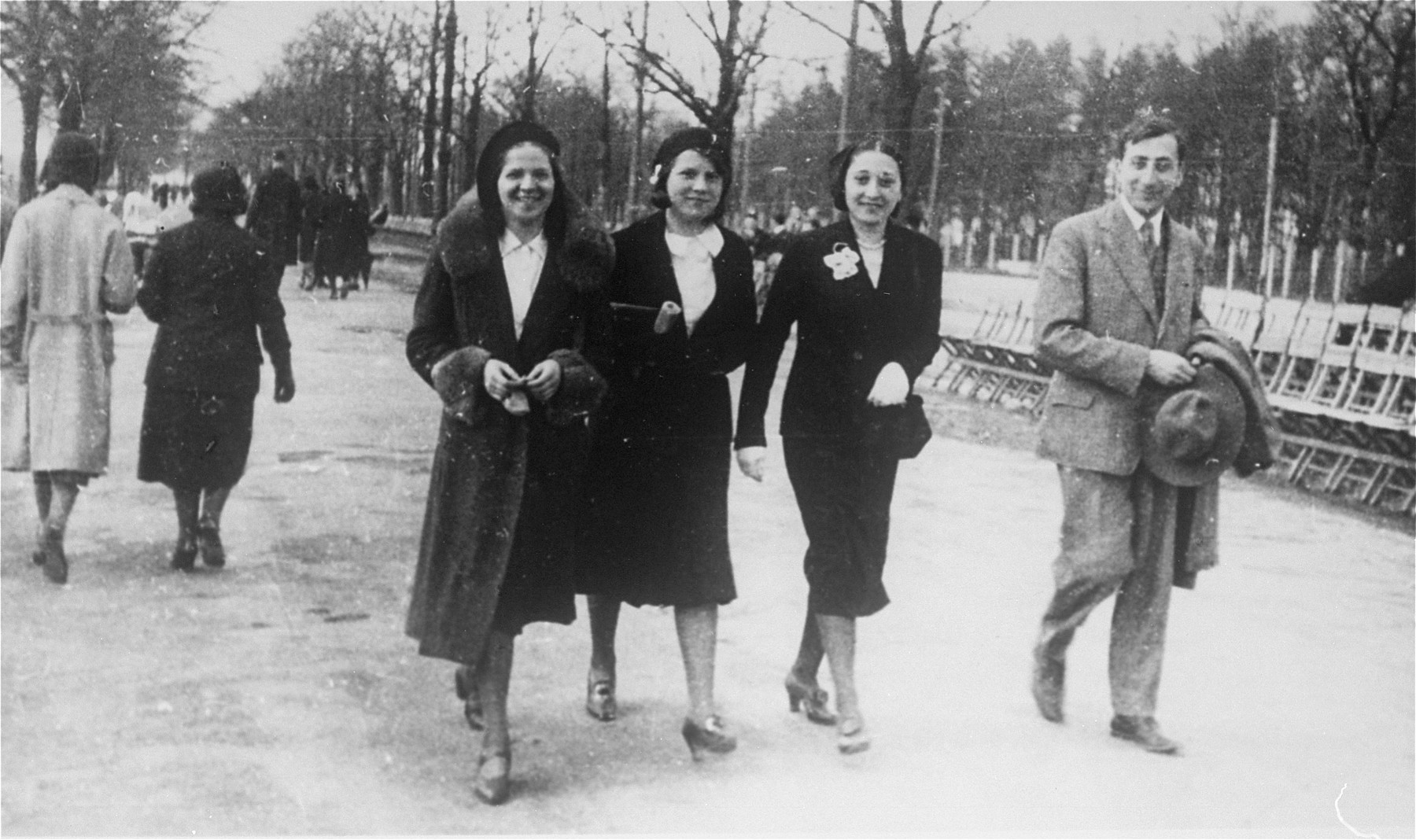 Four Jewish friends walk through a park in Krakow.  Pictured (from left to right) are: Nina Marks, Macka Kepler, Mania Ament, and Gustav Wiecener.  Nina Marks and Gustav Wiecner married in 1934, were deported to the Soviet Union, and later emigrated to Palestine.
