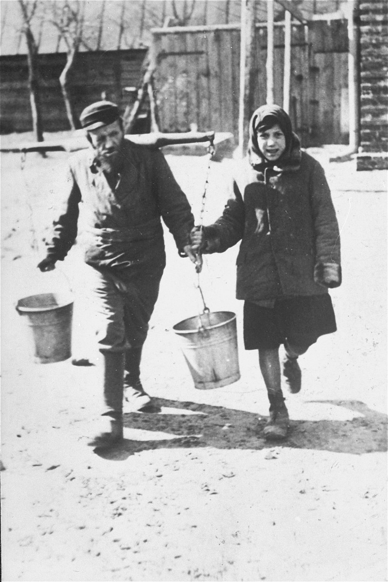 A blind water carrier, Szama (Shmai) Debiowski, and his daughter  Bayla deliver water to Jewish families in town.  Shmai was married to Latta, eight years his junior, and had three younger children, Moishe, Pinchas, and Etta. They resided at #20 Brovarno St, Kozienice. The entire family perished.