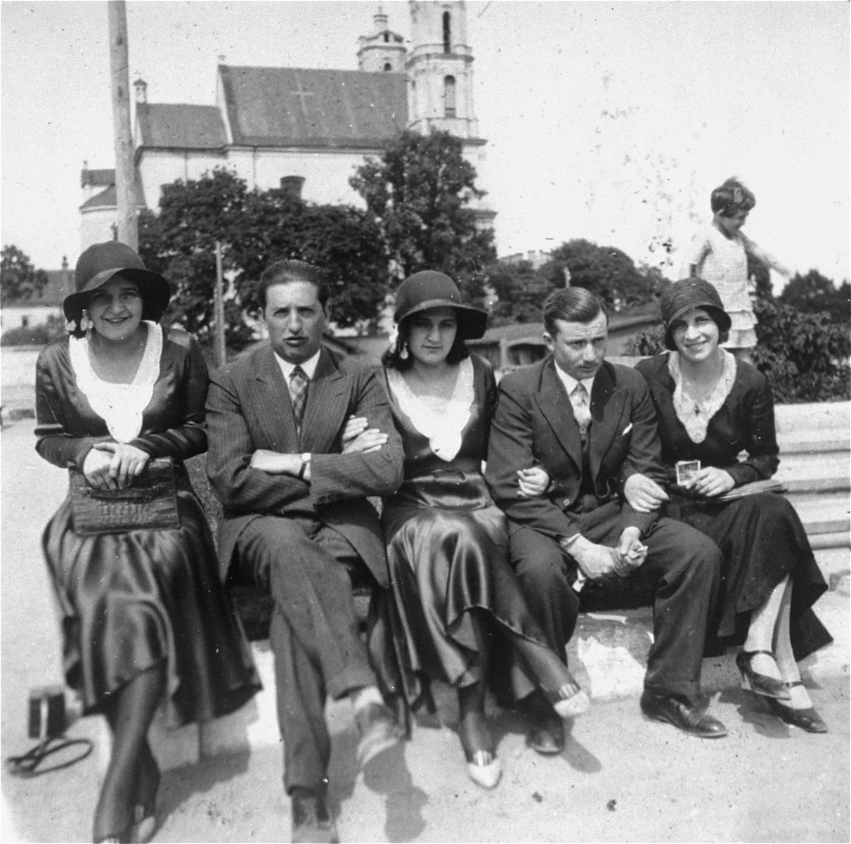 A group of young Jewish men and women sit on a bench in Vilna's Cathedral Square.  Pictured from left to right are: Riva Kugel, Isak Kremer, Etya Kugel (Riva's twin), an unknown friend, and Raya Magid.  Etya and Riva immigrated to Palestine in 1938.