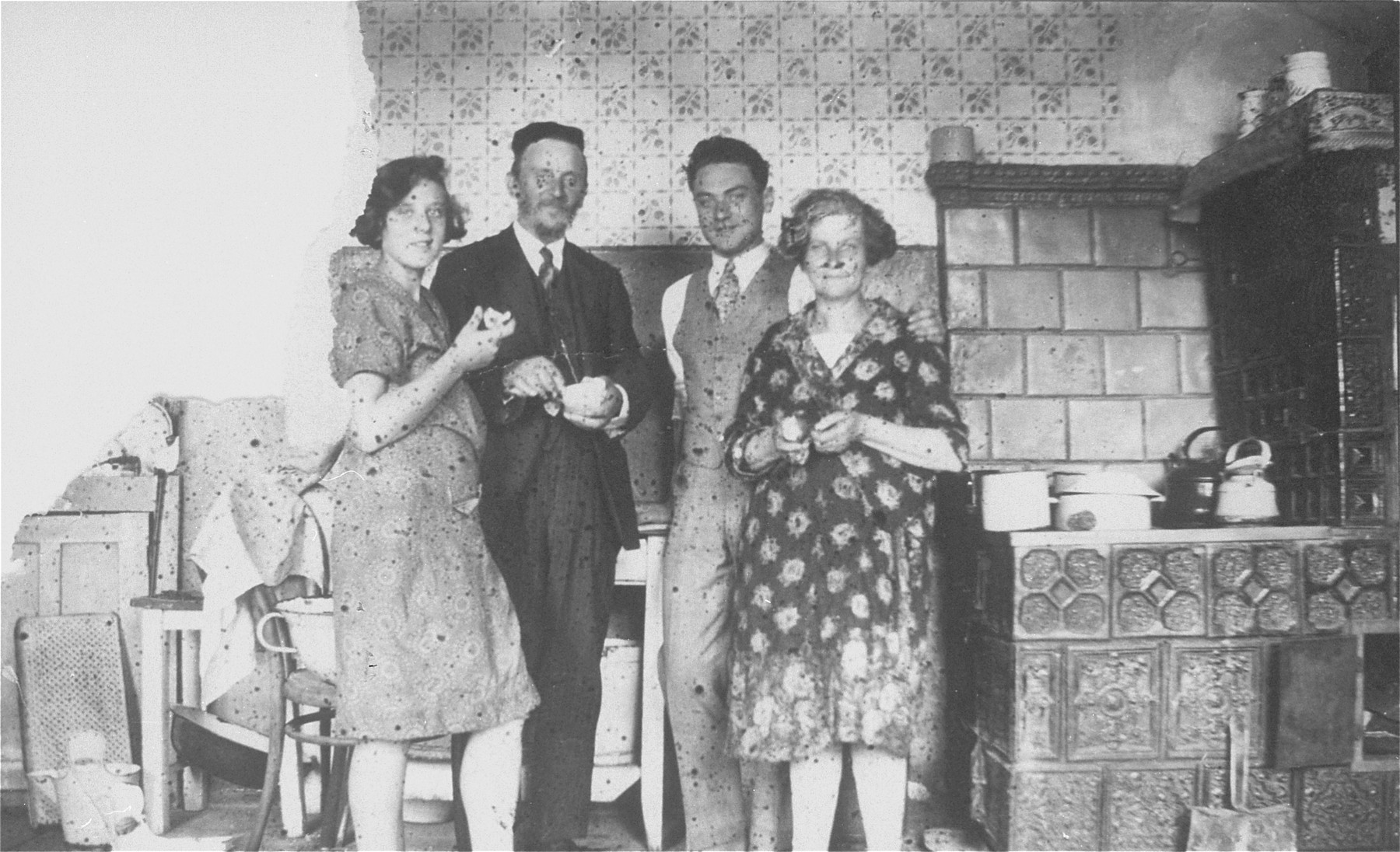 Members of the Ringelheim family pose in their kitchen in Jaroslaw, Poland.  Pictured from left to right are: Chaja, Jacob, David and Miriam Ringelheim.  David is visiting from the United States.  David Ringelheim is the donor's father.