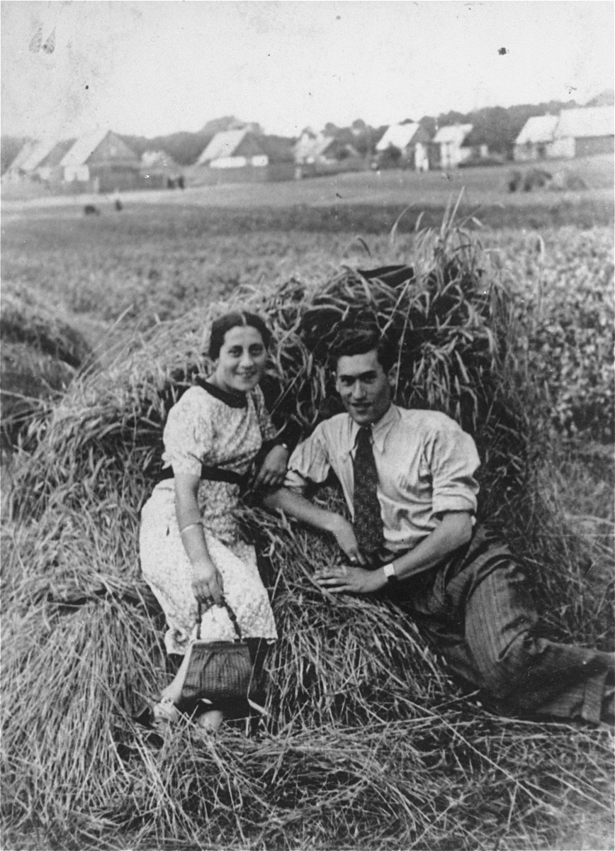 A young Jewish couple sits in front of a haystack in a field.  Pictured are Aaron Tabacznik and his girlfriend, Chana Milgrom.