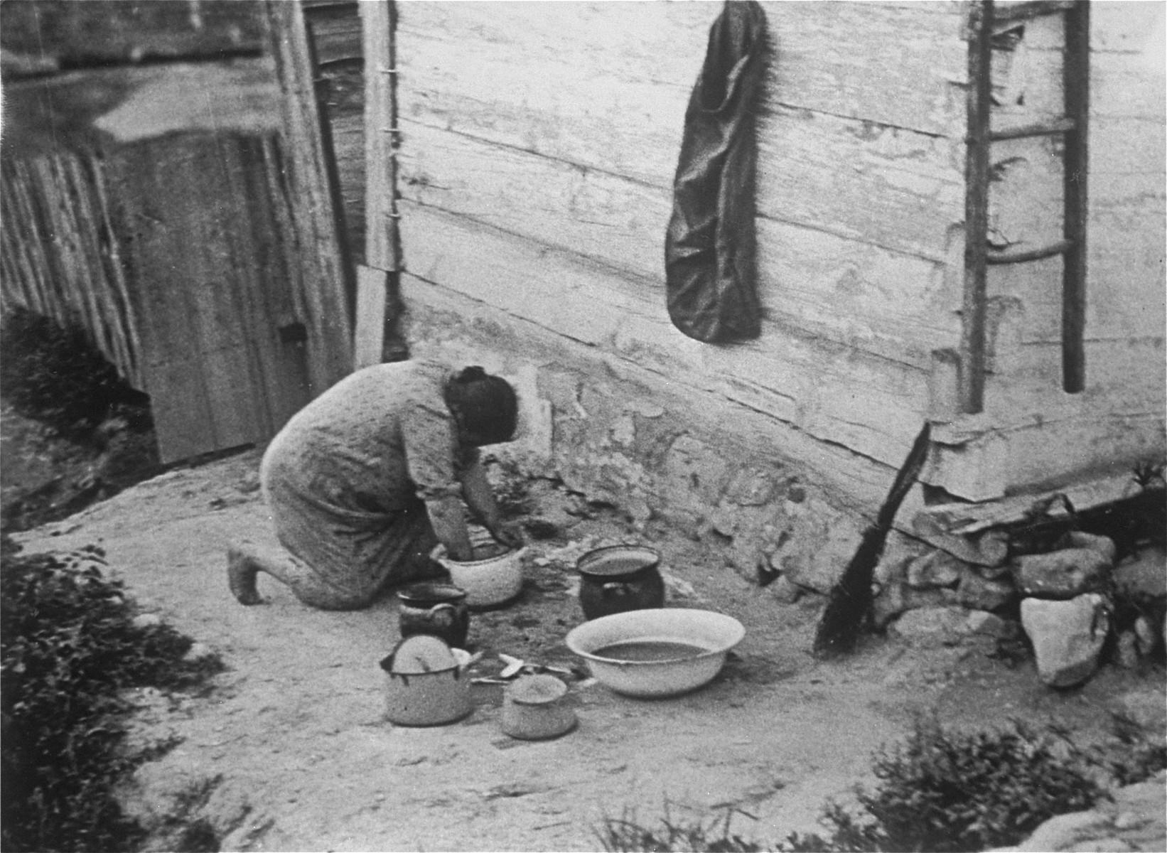 Jewish woman cleaning pots near her house in Kazimierz Dolny.
