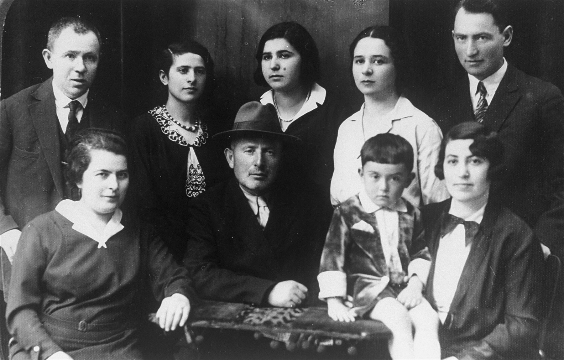 Studio portrait of members of a Jewish family in Vilna.  Pictured are members of the Rudashevsky family.  Among those pictured are: Rosa Rudashevsky (standing second from the left), her father, Zvi Yaacov Rudashevsky (front row center with hat), her sister Yona Rudashevsky (back row, second from the right), Hannah Rudashevsky (back row, center), and Eli Rudashevsky (back row, right), his wife Rosa (a second Rosa, front row, right) and son Yitzhak (front row, second from the right).
