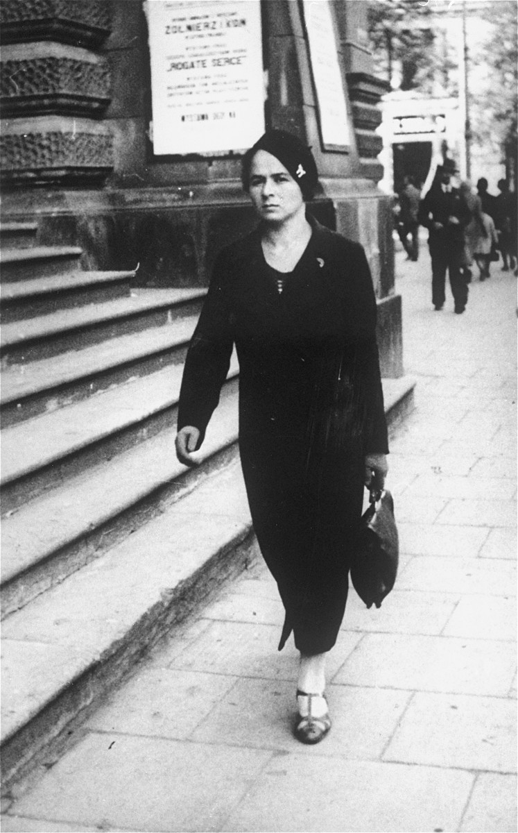 A young Jewish woman walks along a commercial street in Warsaw, Poland.  Pictured is Yona Rudashevsky, the aunt of donor Cilia Rudashevsky.  Yona studied nursing in Vilna and then worked in a Jewish hospital in Warsaw.  In 1935 she immigrated to Palestine, where she worked as a nurse in the Belinson hospital.