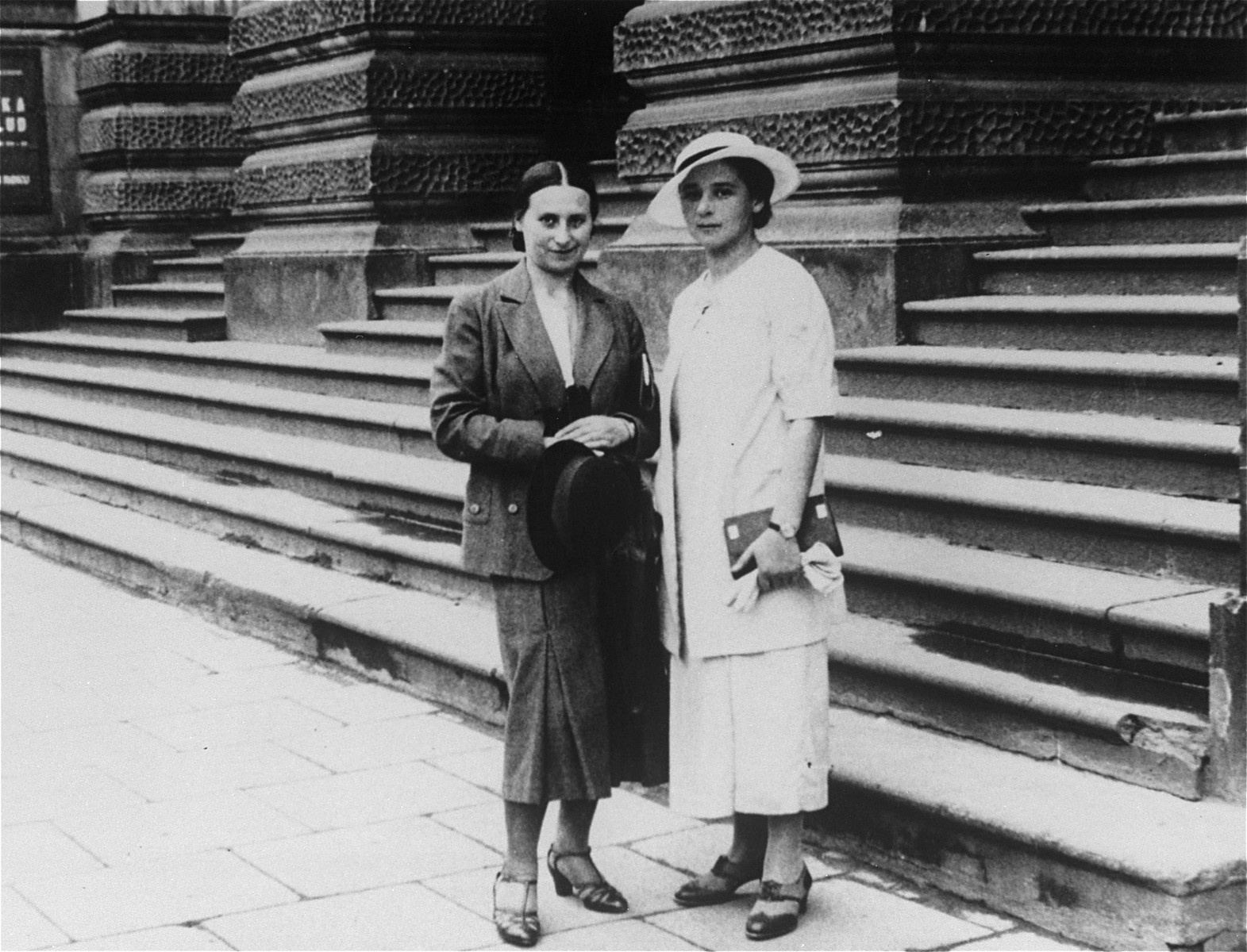 A young Jewish woman poses with a friend on the street in Warsaw, Poland.  Pictured is Yona Rudashevsky (right), the aunt of donor Cilia Rudashevsky.  Yona studied nursing in Vilna and then worked in a Jewish hospital in Warsaw.  In 1935 she immigrated to Palestine, where she worked as a nurse in the Belinson hospital.