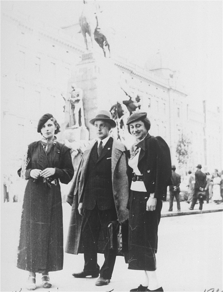 Three young Jewish men and women pose on a street in Krakow during a vacation.  Pictured from left to right are: Raya Magid, an unknown friend and Raya Levin.