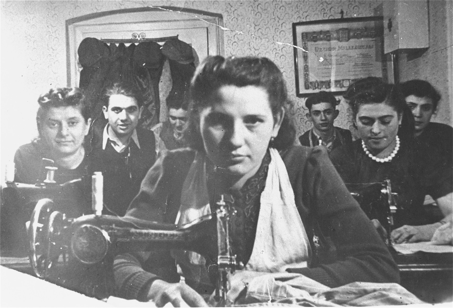 Laborers at work in a Jewish owned garment factory that made children's clothing in Czeladz.  The factory, which belonged to the Urman family, was taken over by the Germans in 1940.  Among those pictured is the donor, Salomon Urman (on the right at the back of the room) and his sister, Pearl Chaya (second row on the right).