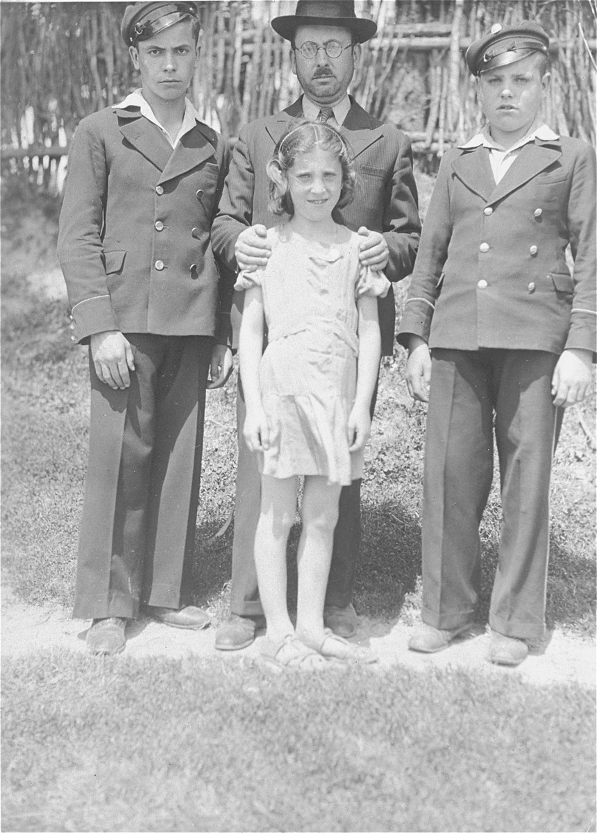Joshua Heilman, (left) with his father, Shraga Feivel, his brother Zev and his sister, Shoshana.  Both boys are wearing school uniforms.  Joshua Heilman immigrated to Palestine on August 22, 1939.  His sister, Shoshana survived Auschwitz concentration camp.  Shraga Feivel and Zev perished.