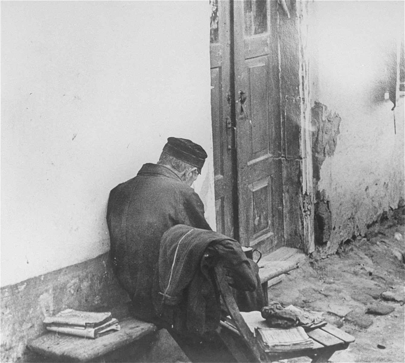 An elderly Jew sitting at an entrance to a house.