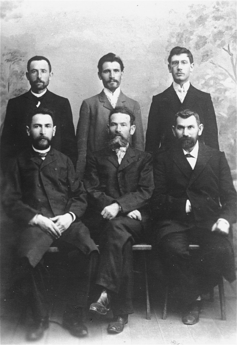 Studio portrait of six Jewish men in Vilna.  Pictured are Abram Magid and his five brothers-in-law.  Among those pictured are Hirsch-Jankl Rudashevsky (top row, left); Cantor Hirsch Ass; Abram Magid, (chief accountant, top row, right); Feivel Garber (owner of the printing plant where the first Hebrew books sent to America were printed); Feodor Mikolayevsky (engraver to the Czar, front row, center); and Leib Eppel (who attended the first Zionist Congress in Basel, front row, right).