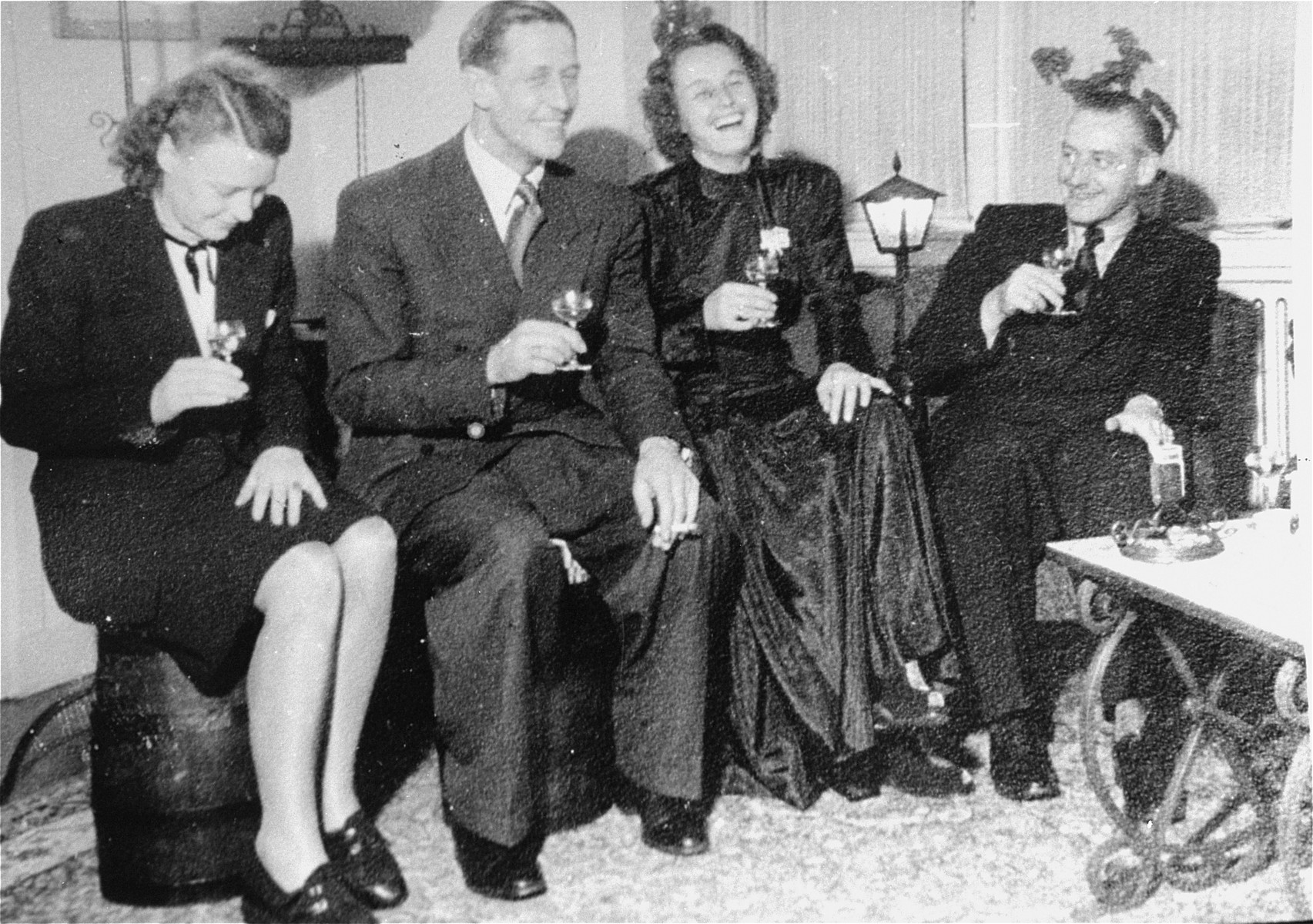SS-Obersturmbannfuehrer Albert Konrad Gemmeker (far right) entertains guests visiting Westerbork for Christmas celebrations.    Pictured from left to right are: Frau Winkelkaemper (secretary of Ferdinand Hugo Aus der Fuenten), SS-Haupsturmbannfuehrer Ferdinand Hugo Aus der Fuenten (Head of the Central Office of Jewish Emigration in Amsterdam), Elisabeth Helena Hassel-Muellender (Gemmeker's mistress) and Gemmeker.  At the time this photo was taken, Gemmeker had only been commandant of Westerbork since the previous October.  He therefore arranged for a banquet to be held at Westerbork in celebration of both Christmas and his new position.
