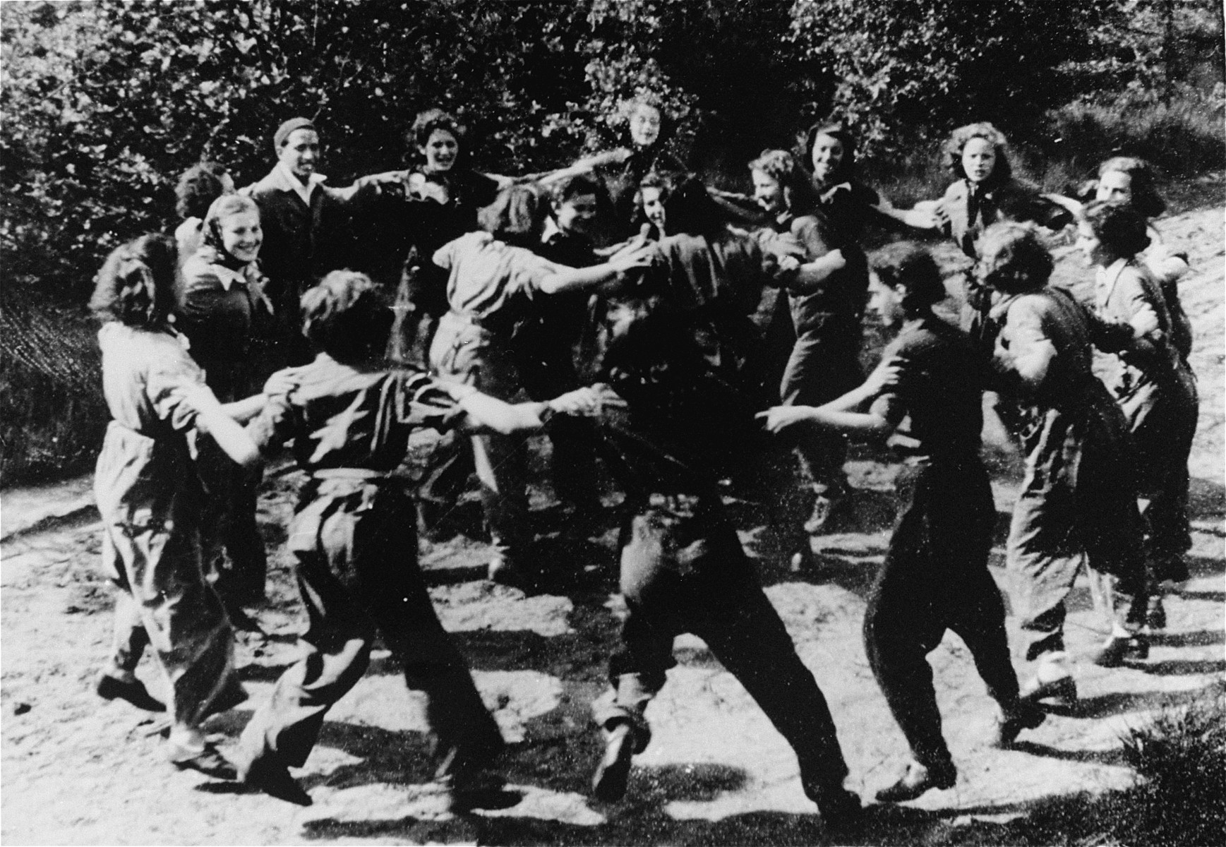 German Jewish youth who are members of a hachshara (Zionist collective) at the Westerbork concentration camp, dance the hora.
