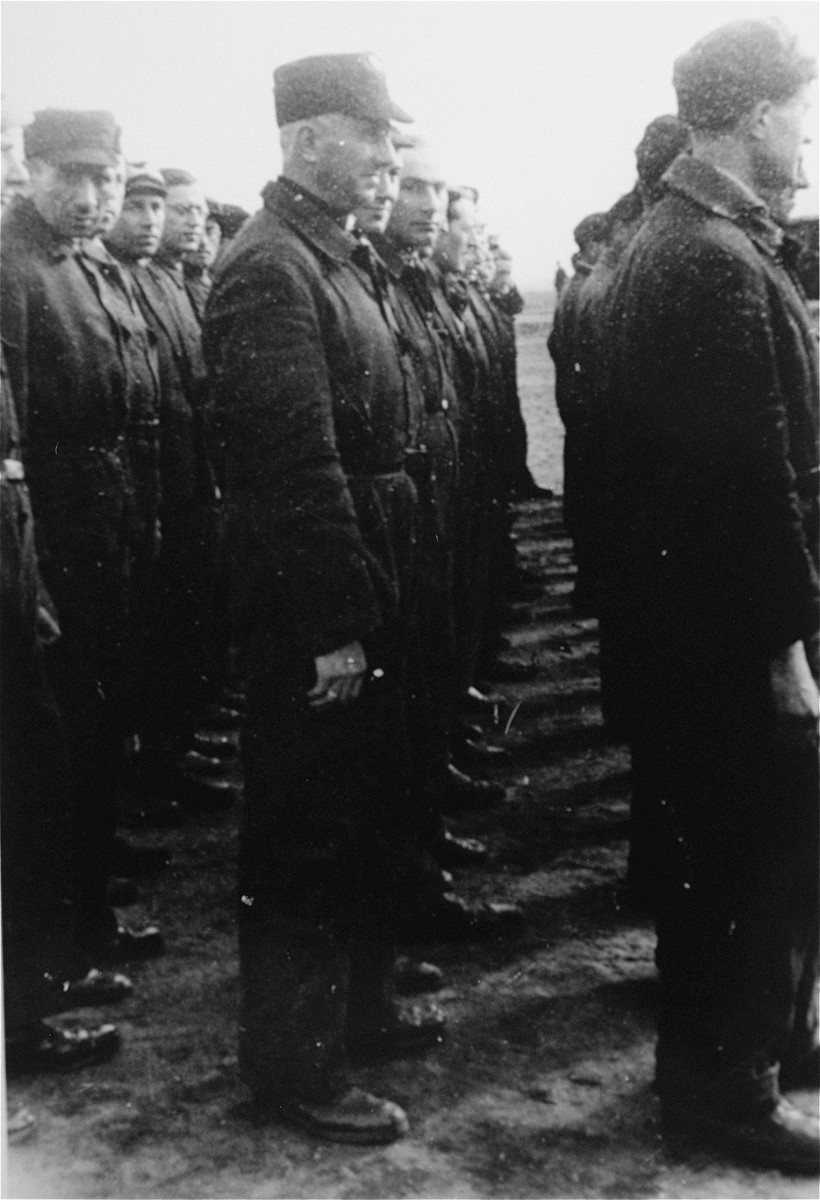 """Jewish police in the Westerbork transit camp stand in formation during a roll call.    Among those pictured is the donor's uncle, Max Levy (in the middle row).  The Jewish police in Westerbork were universally detested by camp inmates for their cruelty and for their collaboration with the Nazis.  Composed  primarily of Dutch and German Jews, the OD was responsible for guarding the punishment block, organizing transports and maintaining order in the camp.  The police force consisted of 20 men in mid-1942, grew to a peak of 182 men in April 1943, and stood at 67 in February 1944.  Wearing the """"OD"""" badge on the left breast was decreed in camp order no. 27 of 23 April 1943."""