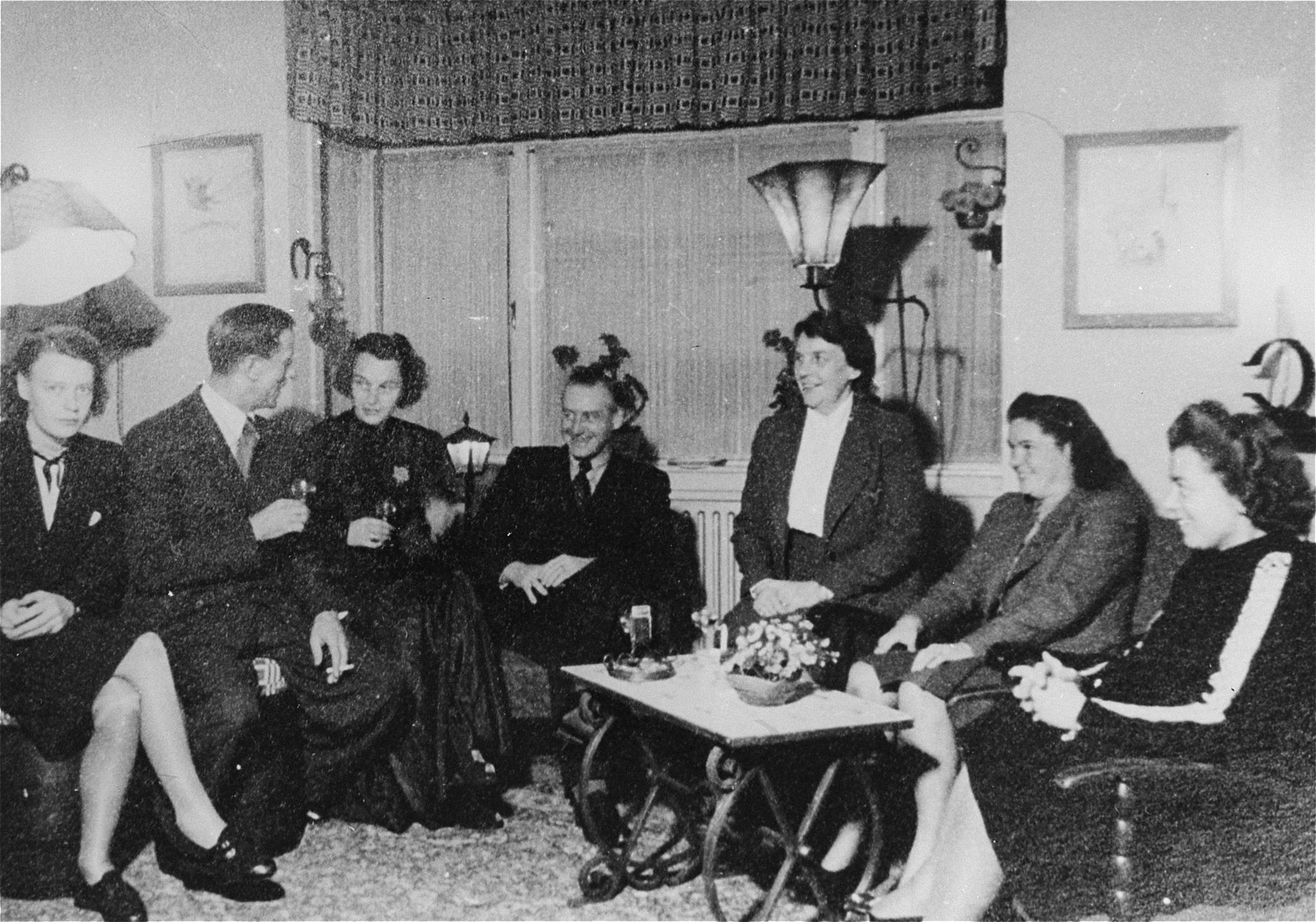 SS-Obersturmbannfuehrer Albert Konrad Gemmeker (center) entertertains guests visiting Westerbork for the Christmas holidays.    Pictured from left to right are: Frau Winkelkaemper (secretary of Ferdinand Hugo Aus der Fuenten), SS-Haupsturmbannfuehrer Ferdinand Hugo Aus der Fuenten (Head of the Central Office of Jewish Emigration in Amsterdam), Elisabeth Helena Hassel-Muellender (Gemmeker's mistress) and Gemmeker.  The three women at right are unidentified.  At the time this photo was taken, Gemmeker had only been commandant of Westerbork since the previous October.  He therefore arranged for a banquet to be held at Westerbork in celebration of both Christmas and his new position.