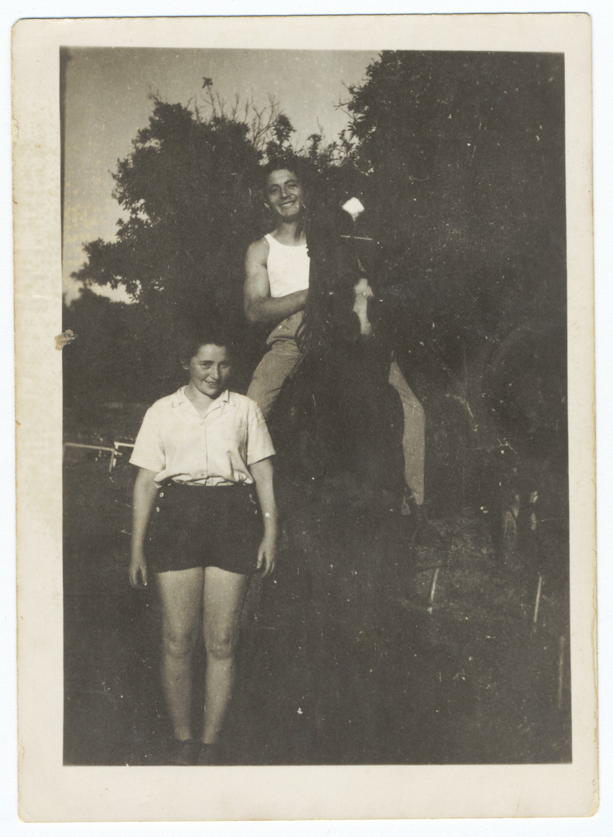 A young man on a horse poses next to his girlfriend in Kibbutz Gan Shmuel.  Pictured are Miriam Domawaska and Josef Fischer.