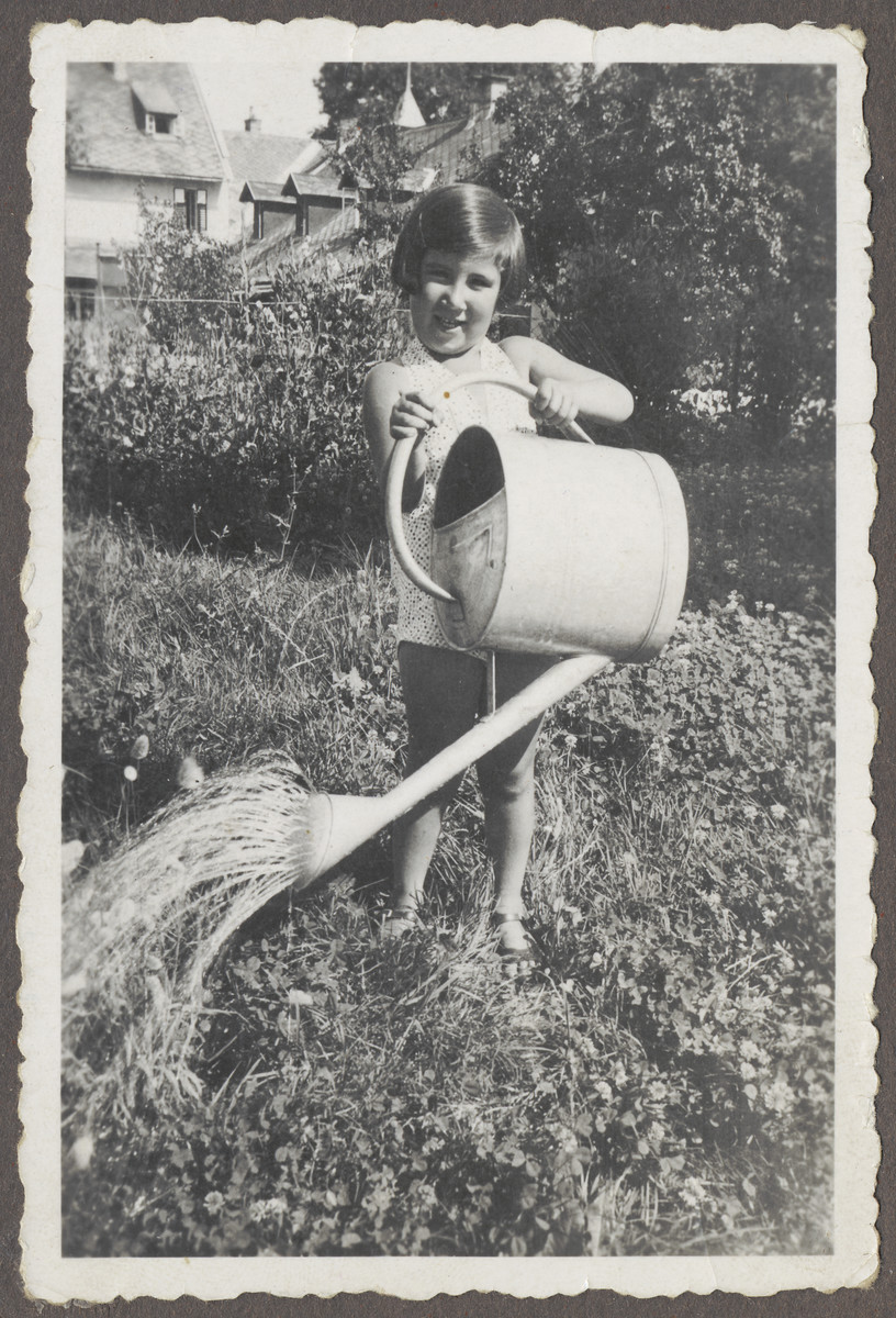 Ruth Landau, an Austrian Jewish girl, waters her garden with a large watering can.