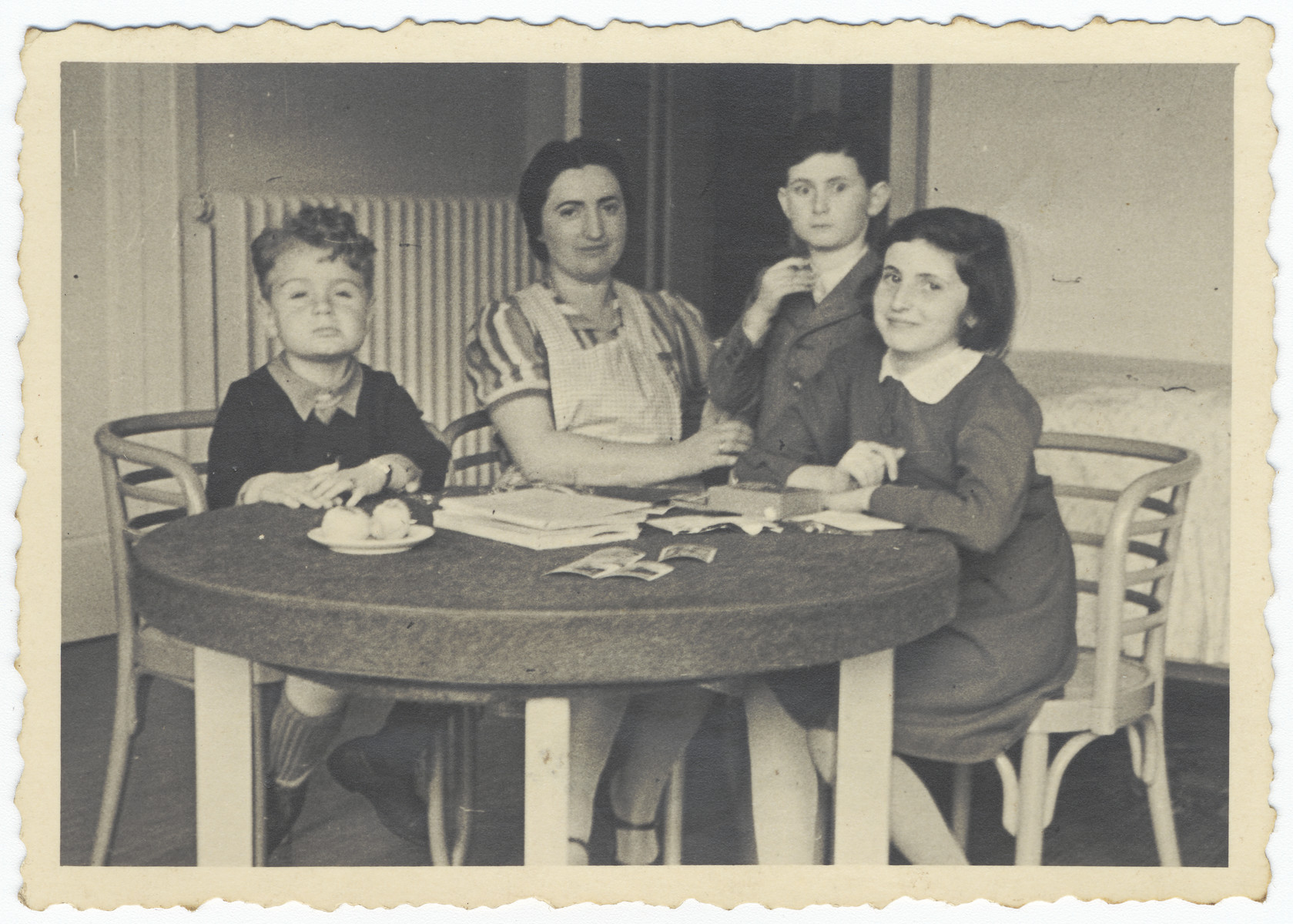 A mother, her two children and a friend sit around a round-wooden table.    Pictured are Frieda Zeilender, the aunt of the donor, and her two children to her right, Dolly and Ralf.  All perished in the Holocaust. The photograph was saved by a family who rented  room in their building and helped provide them with food.