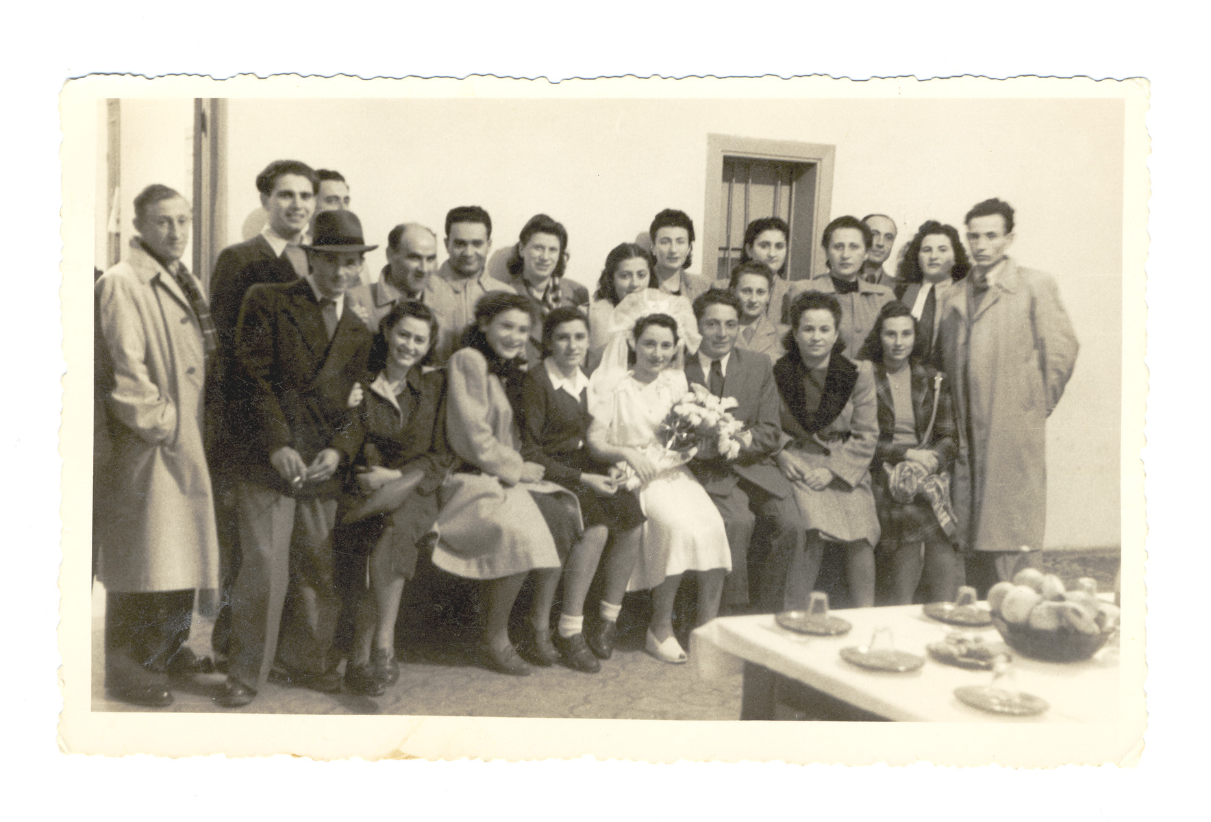 A recent immigrant couple poses on their wedding day surrounded by friends from an Italian displaced persons' camp and the illegal immigration ship, the Wingate.  Almost immediately after the wedding, the groom left to fight with the Haganna in the battles preceding the War of Independence.  Pictured in the center or Josef Fischer and his bride, Miraim Domawaska Fischer.  Next to Miriam is her sister Rivke Domawaska.  Next to Josef is Malka Yevelewicz who survived as a partisan.