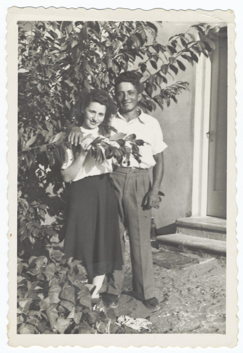 Close-up portrait of a young couple standing next to a tree in a garden of Kibbutz Gan Shmuel.  Pictured are Miriam Domawaska and Josef Fischer.