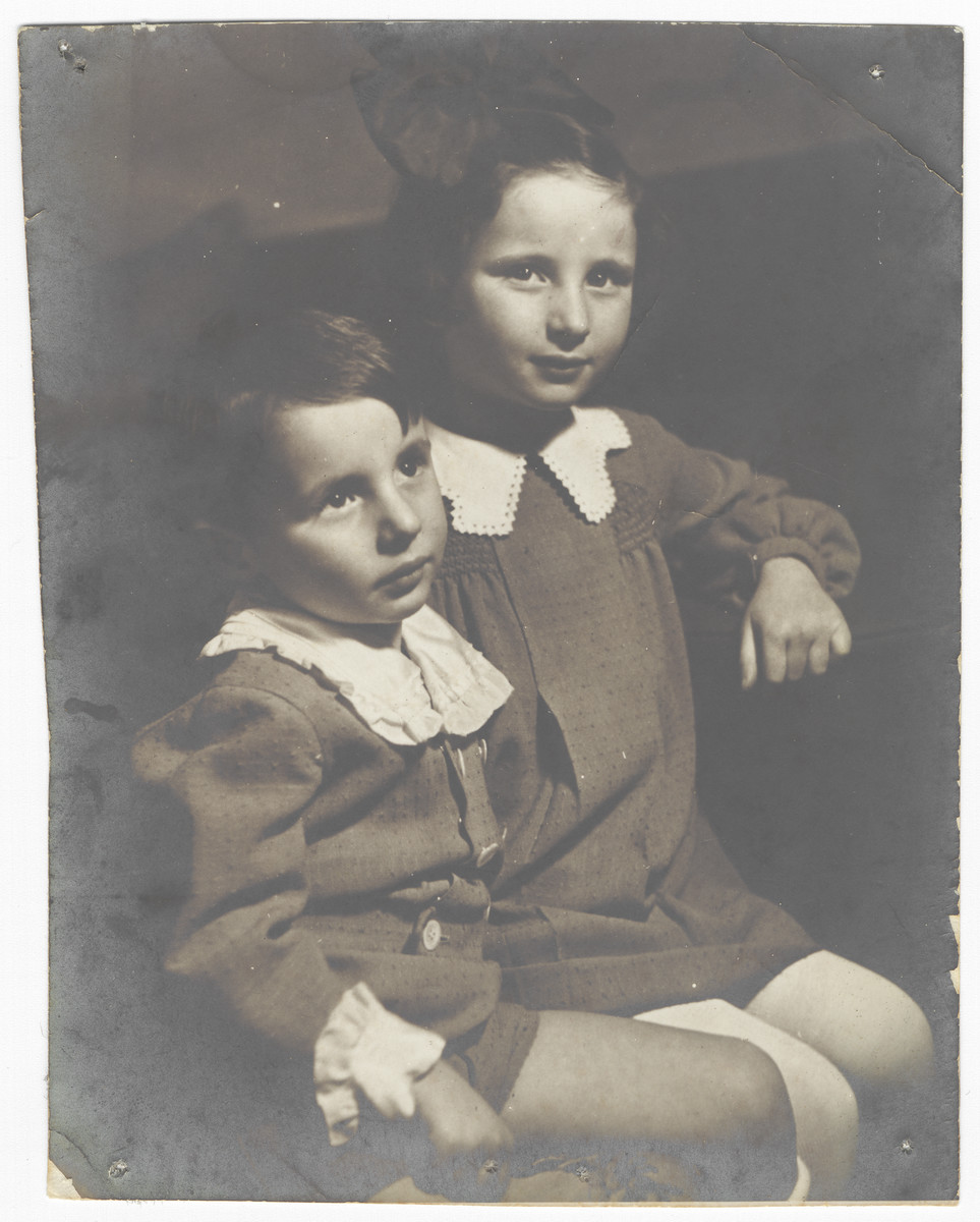 Studio portrait of two young Jewish siblings in Krakow, Poland.  Pictured are Aleksander and Janina Schlachet.