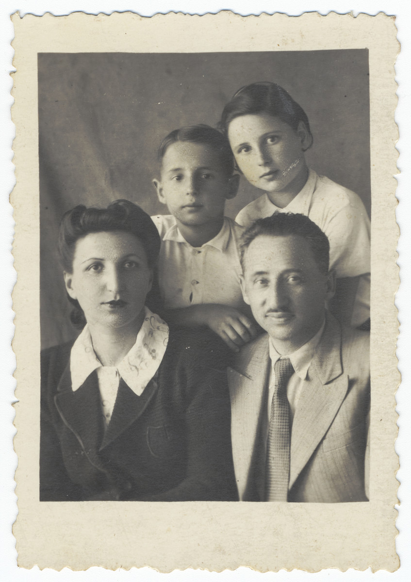 Studio portrait of a Polish Jewish family in Uzbekistan.  Pictured are Lotte and Herman Schlachet and their children, Janina and Aleksander.