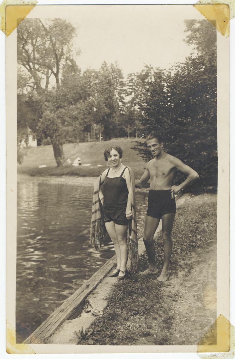 An Jewish couple wearing bathing suits poses next to a lake.  Pictured are Sarafina (Hochstaet) Landau and Jacob Landau.