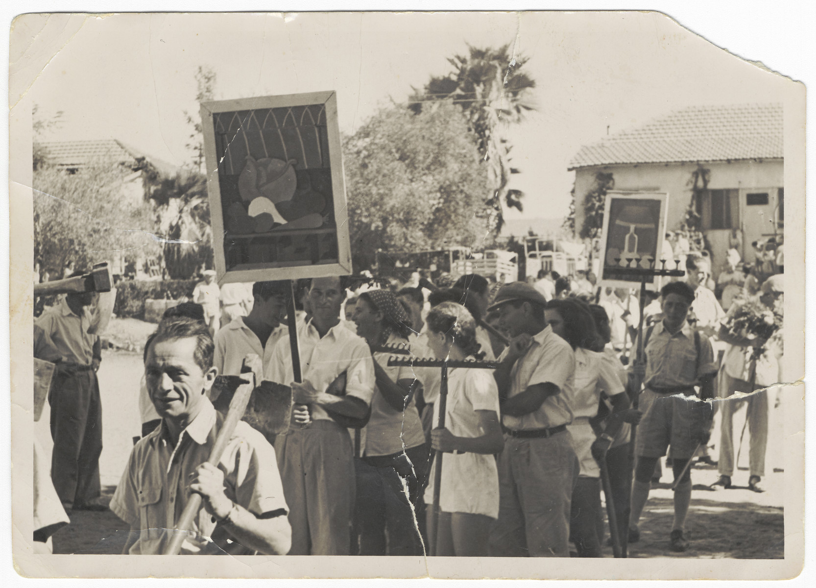 Members of a Shomer Hatzair Kibbutz, Gan Shmuel, parade on May Day with tools and banners illustrating their occupations.  Among those pictured is Josef Fischer who is carrying a hose to symbolize his work spraying crops for insects.