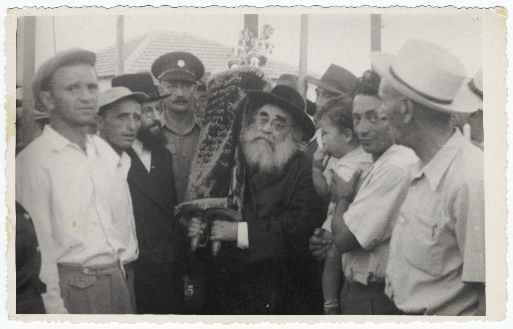A rabbi, surrounded by congregants, carries in a new torah scroll in the settlement, Kiryat Bialik.  Pictured on the right is Josef Fischer holding his young son, Zev.