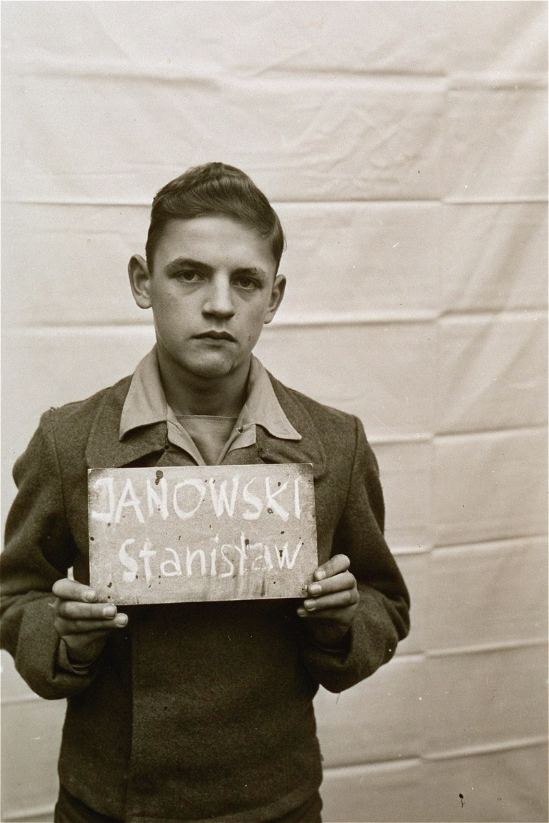 Stanislaw Janowski holds a name card intended to help any of his surviving family members locate him at the Kloster Indersdorf DP camp.  This photograph was published in newspapers to facilitate reuniting the family.