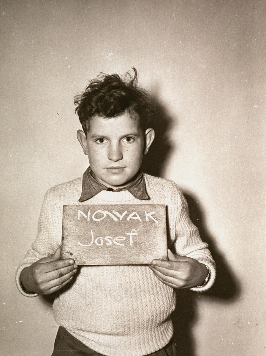 Josef Nowak holds a name card intended to help any of his surviving family members locate him at the Kloster Indersdorf DP camp.  This photograph was published in newspapers to facilitate reuniting the family.