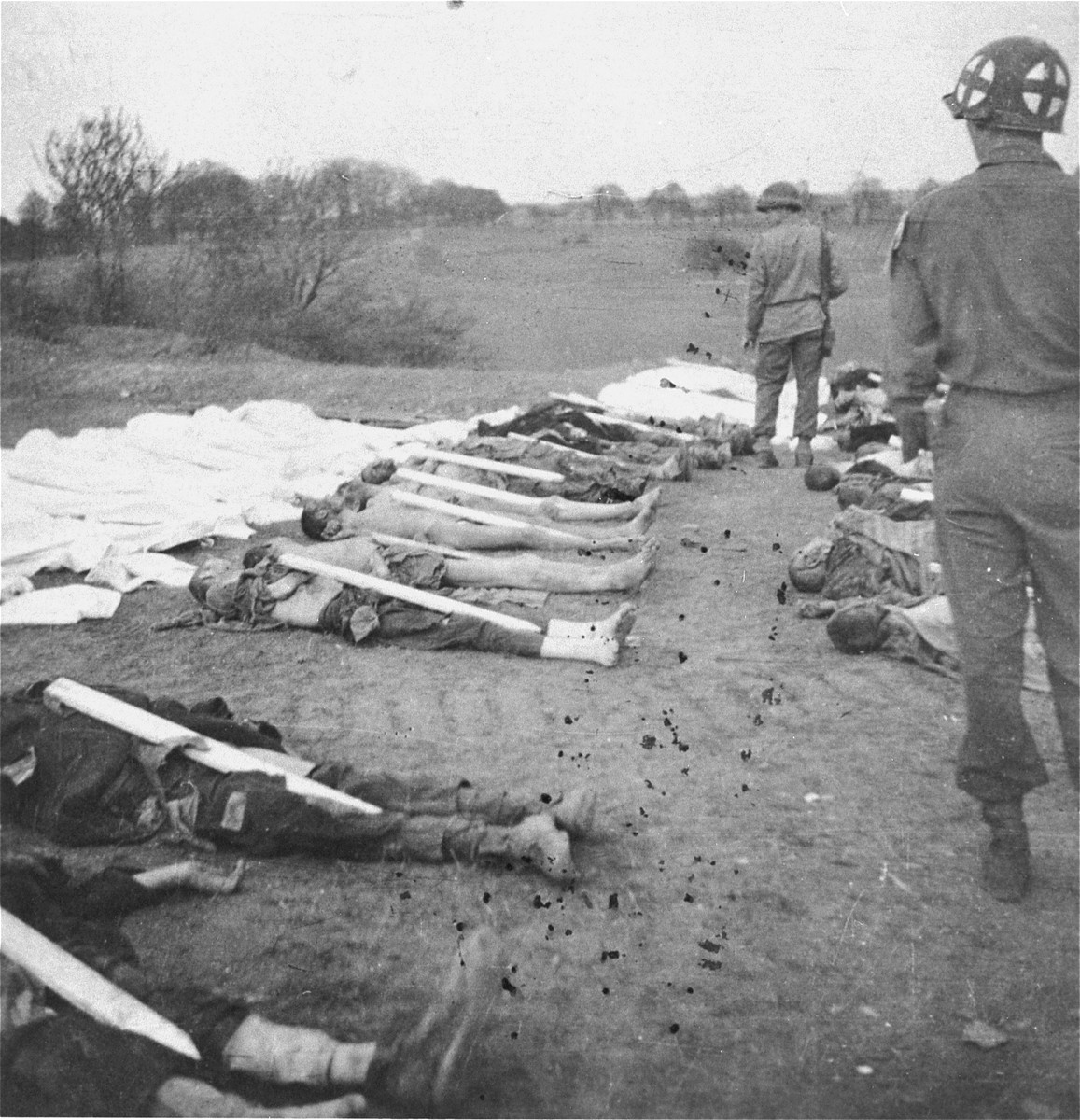 An American soldier and medic walk among corpses found in the Ohrdruf concentration camp.