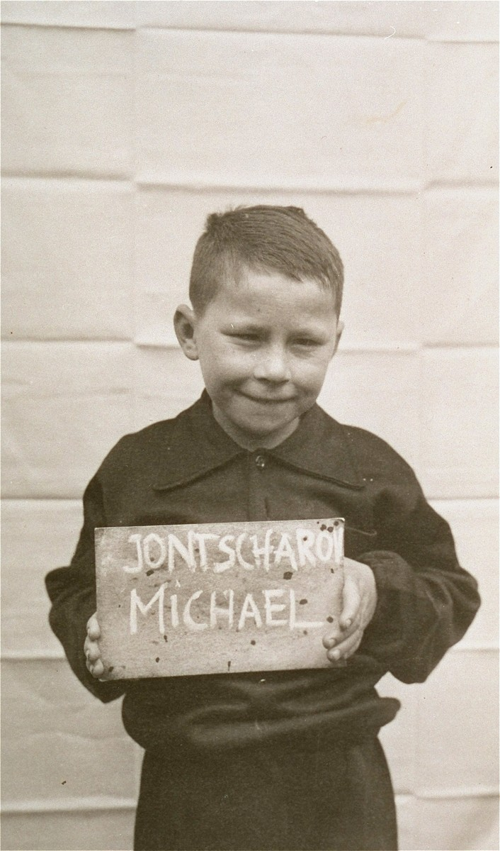 Michael Jontscharon holds a name card intended to help any of his surviving family members locate him at the Kloster Indersdorf DP camp.  This photograph was published in newspapers to facilitate reuniting the family.
